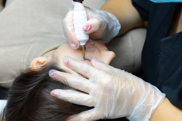 Un tatoueur réalise un maquillage permanent des cils