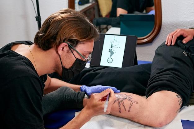Un tatoueur regardant une tablette et dessinant un tatouage sur la jambe d'un homme dans un studio