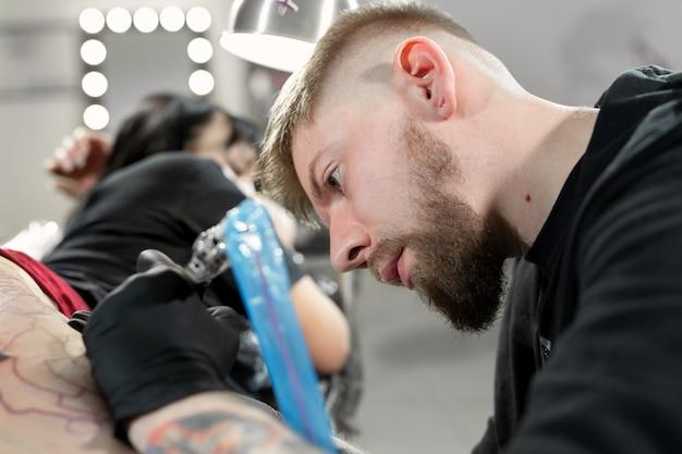Tatoueur tatouant une femme