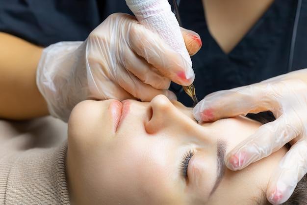 Tatoueur en train de travailler sur le maquillage permanent des paupières