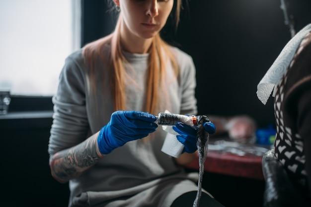 Une tatoueuse en gants stériles bleus prépare la machine à tatouer, maître en salon. tatouage professionnel en studio