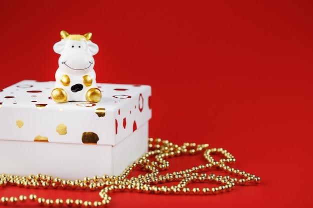 Taureau jouet du nouvel an 2021 avec un cadeau sur fond rouge.