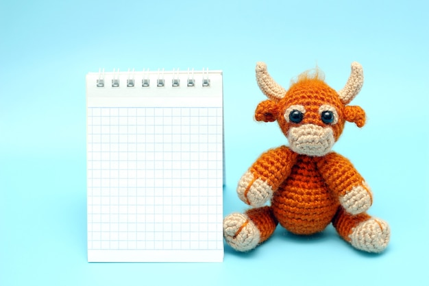 Taureau jouet marron tricoté à côté d'un bloc-notes