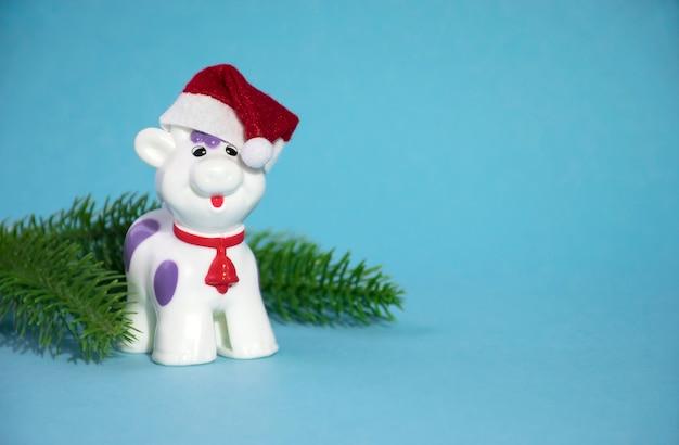 Taureau de noël ou jouet de vache en bonnet rouge avec des branches de sapin vert.