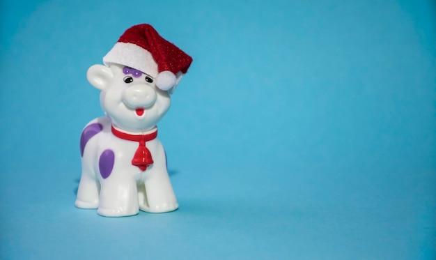 Taureau de noël ou jouet de vache en chapeau de nouvel an rouge et cloche rouge sur le cou comme symbole de l'année 2021