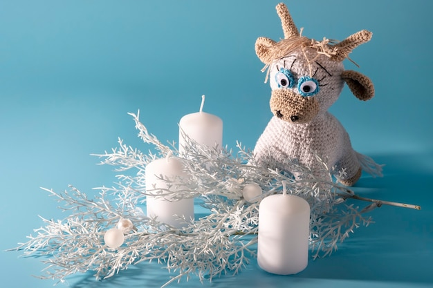 Le taureau tricoté blanc est un symbole de la nouvelle année 2021. des bougies de gobie et une brindille de noël blanche