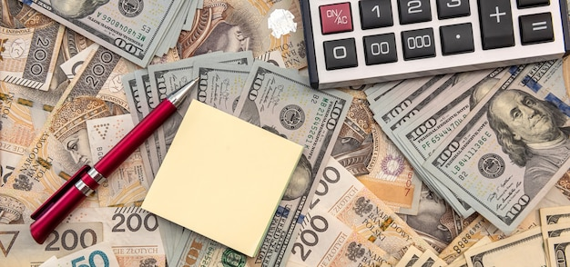 Taux de change entre les billets de dollar et de zloty de pologne. stylo et note avec calculatrice