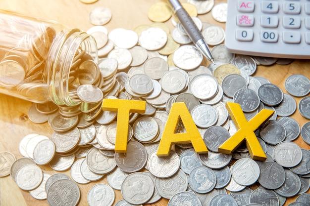 Tax concept.texte de la taxe sur les pièces de monnaie avec un stylo et une calculatrice sur la table