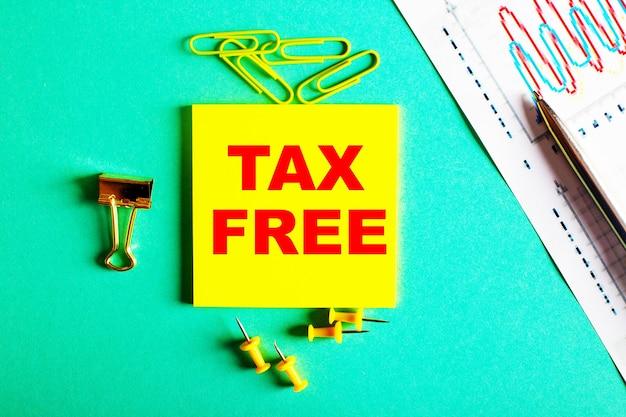 Tax free est écrit en rouge sur un autocollant jaune sur un mur vert près du graphique et du crayon