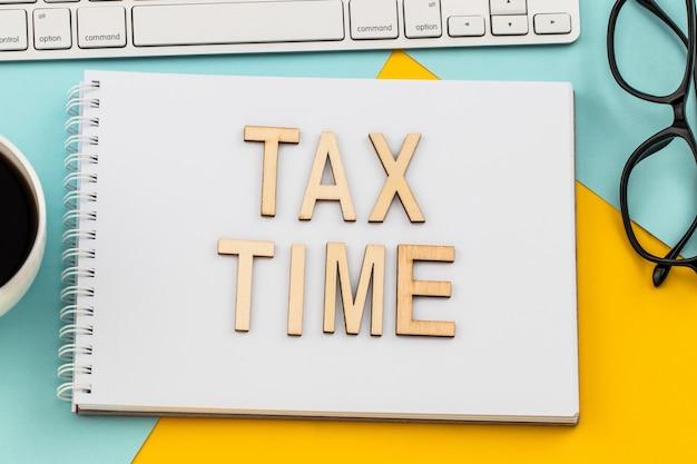 Tax time lettres en bois avec formulaire d'impôt et tasse de café.