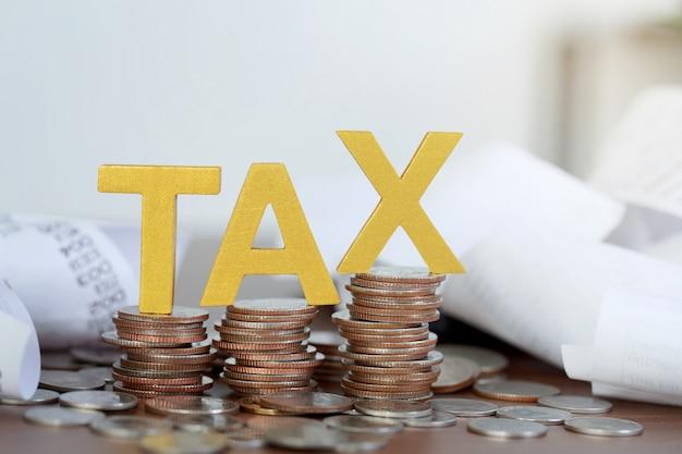 Taxe concept.word taxe mis sur les pièces et facture papier avec des pièces sur les bureaux.