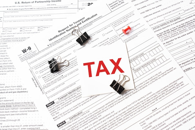 Taxe écrite sur une note d'autocollant blanc avec un trombone au formulaire d'impôt