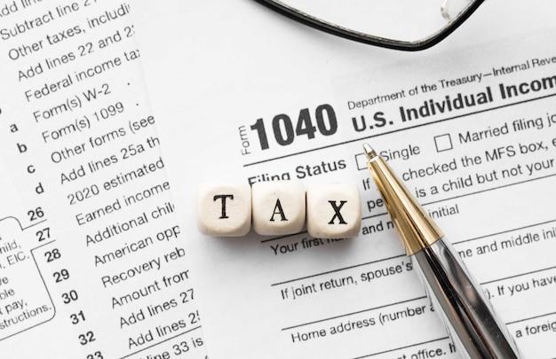 Taxe de mot sur un cube en bois. formulaire standard américain de déclaration de revenus 1040.