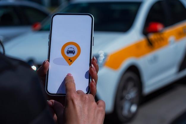 Taxi en ligne dans un smartphone. la fille tient le téléphone dans ses mains avec une application mobile à l'écran sur fond de voiture.