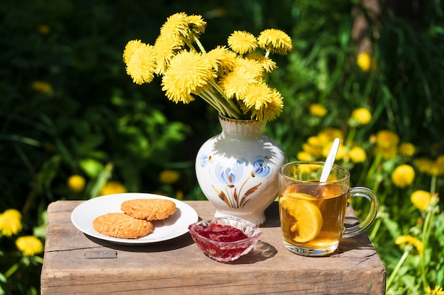 Tea party avec biscuits et confiture dans le jardin sur fond de fleurs