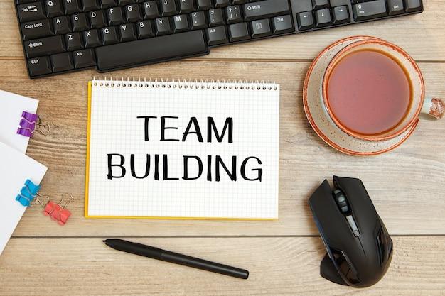 Team building est écrit sur un bloc-notes sur un bureau avec des accessoires de bureau.
