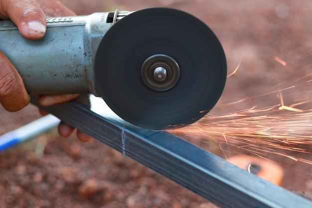 Technicien en acier de coupe avec un outil sur le lieu de travail.