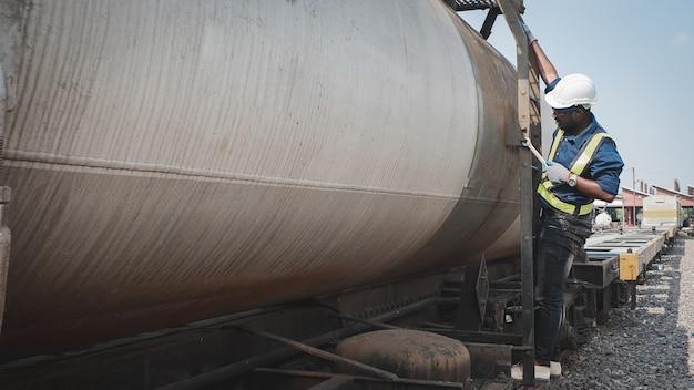 Un technicien africain d'ingénieurs en machines portant un casque, des bosquets et un gilet de sécurité utilise une clé pour réparer le gaz et le pétrole de transport ferroviaire