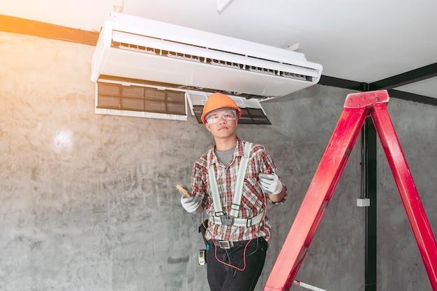 Technicien de l'air dans l'ensemble standard de sécurité vérification de la qualité du climatiseur nouvellement installé.