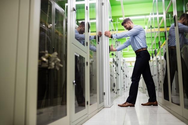 Technicien ajustant l'armoire serveur