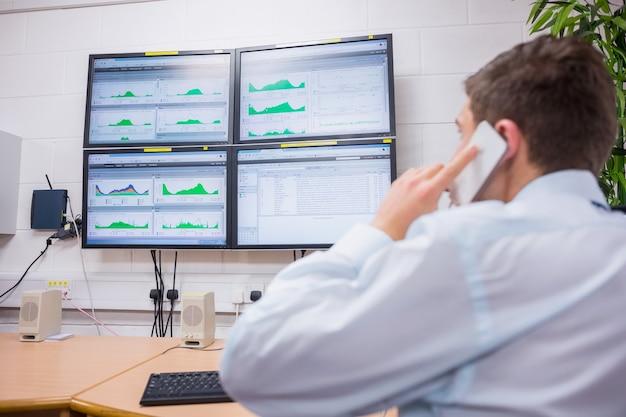 Technicien en appelant et en regardant l'écran d'ordinateur
