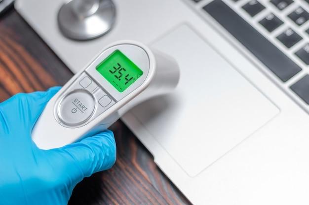 Le technicien applique un thermomètre infrarouge sur le panneau de l'ordinateur portable.