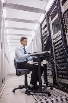 Technicien assis sur une chaise pivotante en utilisant un ordinateur portable pour diagnostiquer les serveurs