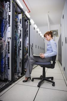 Technicien assis sur un fauteuil pivotant utilisant un ordinateur portable pour diagnostiquer les serveurs