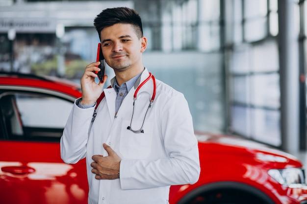 Technicien automobile avec stéthoscope dans une salle d'exposition automobile parlant au téléphone