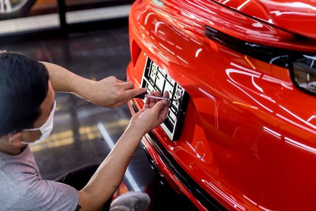 Technicien changeant le numéro de plaque d'immatriculation en service