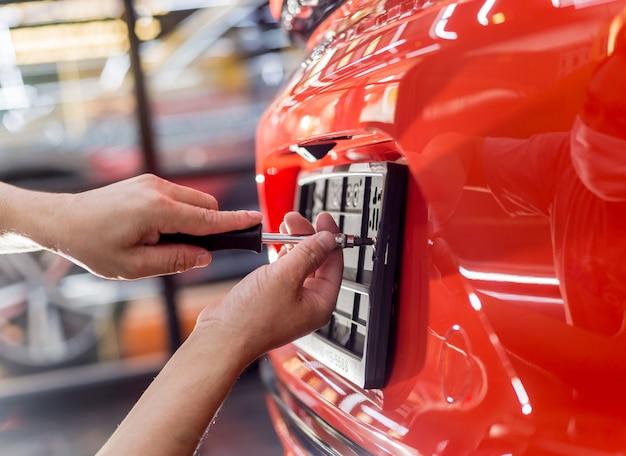 Technicien changeant le numéro de plaque de voiture dans le centre de service.