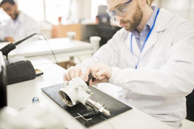 Un technicien concentré découvre la raison de la rupture du transducteur