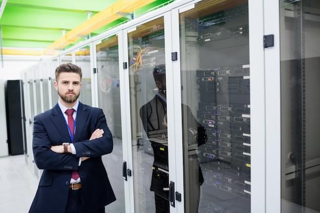 Technicien debout avec les bras croisés dans une salle de serveurs