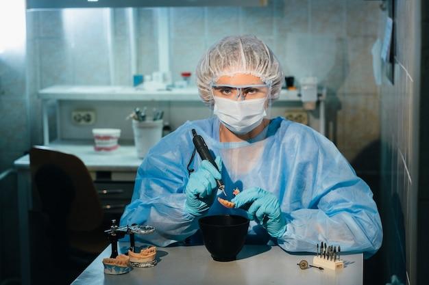 Un technicien dentaire masqué et ganté travaille sur une dent prothétique dans son laboratoire