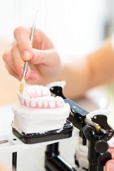 Technicien dentaire produisant une prothèse dentaire
