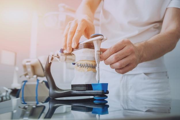 Technicien dentaire travaillant avec articulateur en laboratoire dentaire