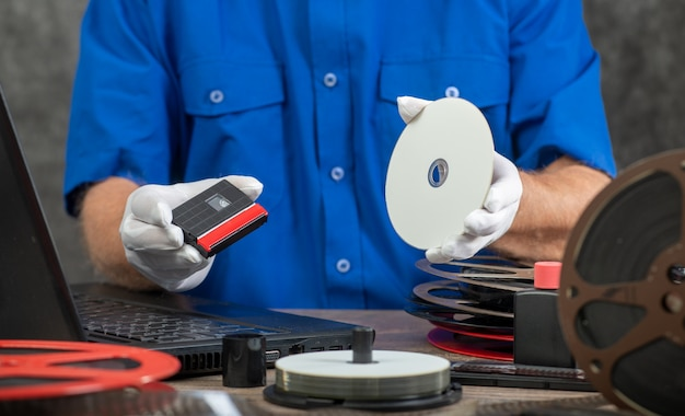 Technicien avec des gants blancs numérisant une mini-cassette dv