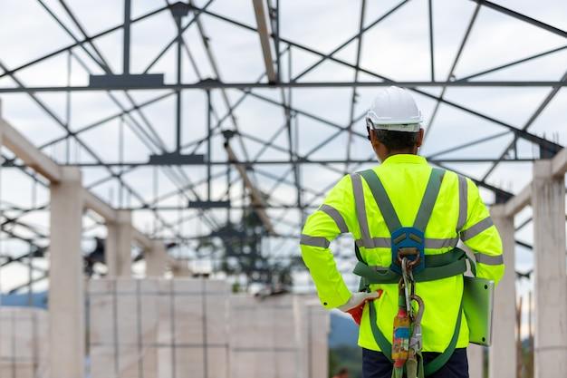 Technicien ingénieur asiatique regardant le contrôle de la construction dans la construction de structures de toit sur la construction