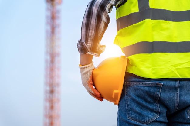 Technicien ingénieur tenant un casque sur un chantier de construction en gros plan
