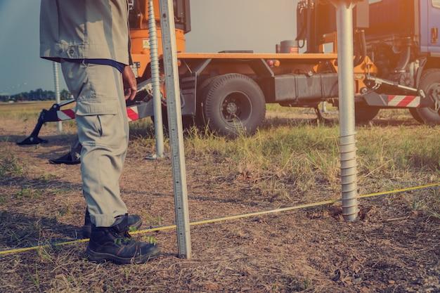 Technicien installant la vis de terre pour la structure de support du panneau solaire à la ferme solaire