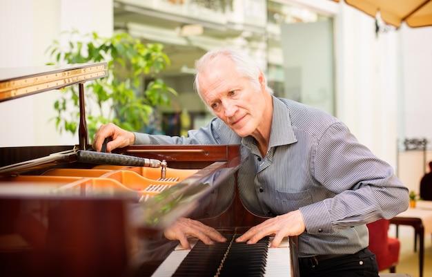 Technicien en instrument de musique âgé accordant un clavier de piano.