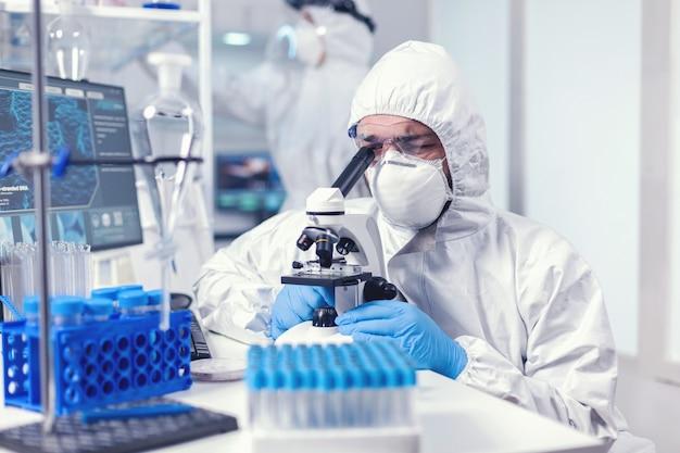 Technicien de laboratoire en équipement ppe examinant des échantillons de virus au microscope en laboratoire. scientifique en tenue de protection assis sur le lieu de travail utilisant la technologie médicale moderne pendant l'épidémie mondiale.