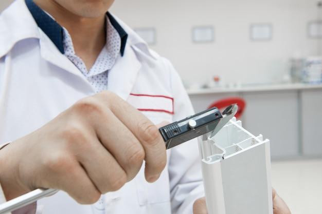 Le technicien de laboratoire mesure le profil en plastique avec un pied à coulisse numérique