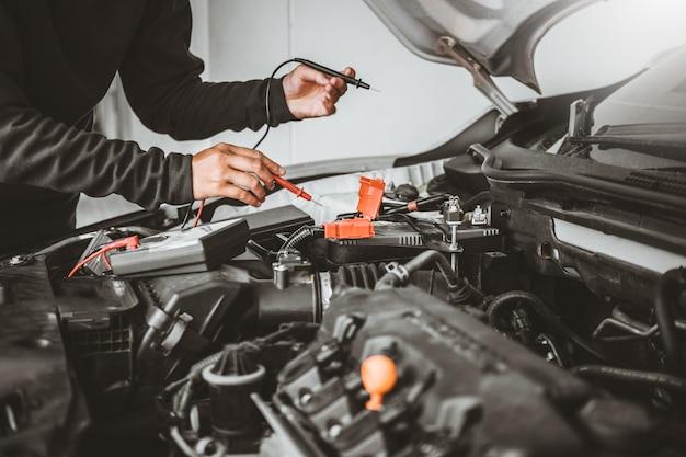 Technicien mains de mécanicien automobile travaillant dans la réparation automobile