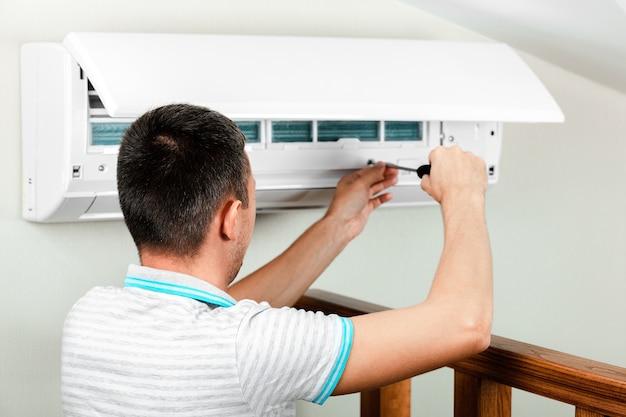 Technicien masculin nettoyage du climatiseur à l'intérieur