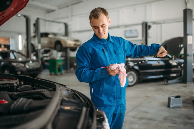 Technicien masculin travaille avec moteur de voiture