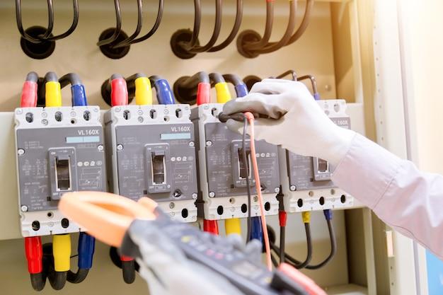 Le technicien mesure la tension ou le courant par voltmètre dans le panneau de commande