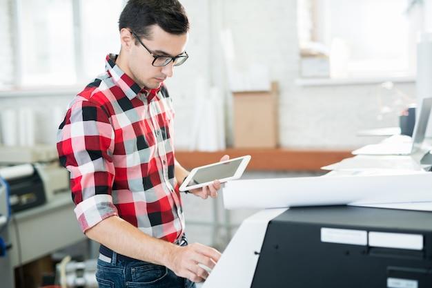 Technicien occupé travaillant avec imprimante