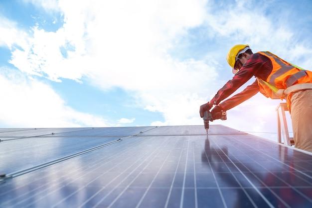 Technicien de panneaux solaires avec perceuse pour l'installation et l'entretien de panneaux solaires sur le toit d'une centrale solaire,panneau solaire,source d'électricité alternative.