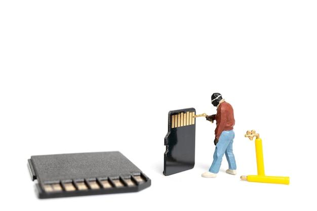 Technicien de personnes miniature fixant des tas de cartes sd sur fond blanc
